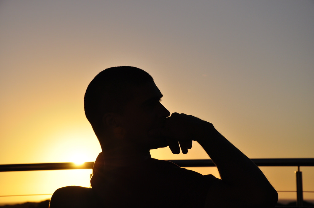 """A man sitting down in """"The Thinker"""" pose."""