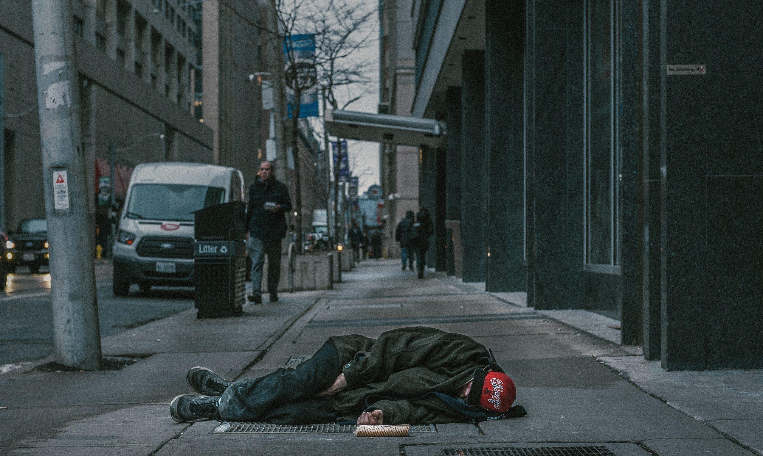 Homeless person sleeping on the sidewalk.