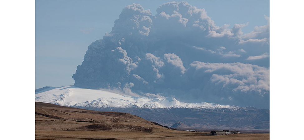 A photograph of an erupting volcano. A giant plume of gas and dust can be seen being ejected from it.