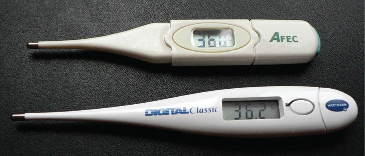 Picture is a photograph of two digital oral thermometers.