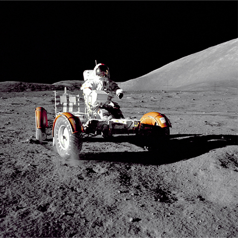 A photograph of an astronaut driving the lunar rover on the moon. The image and the shadow of the rover are very sharp. The sky is dark.