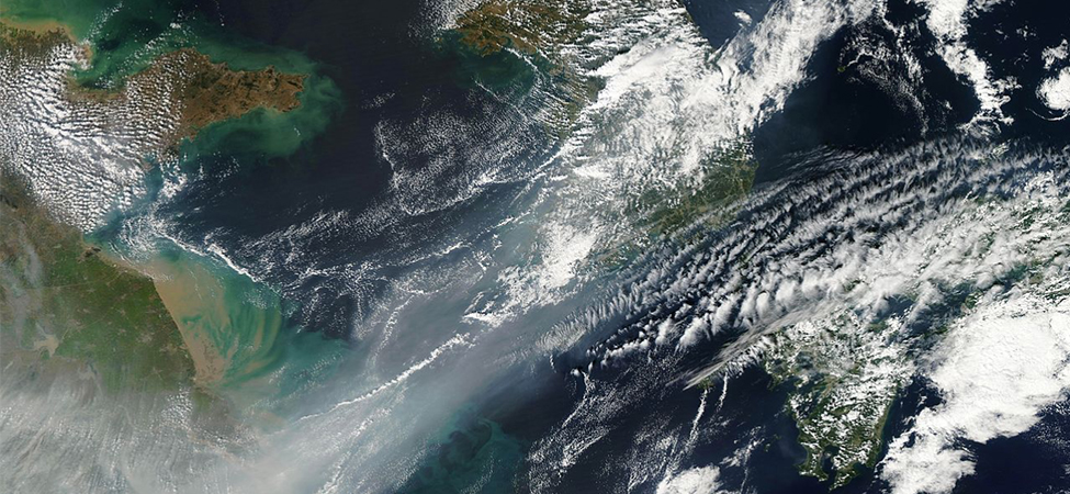 A satellite photograph of northeastern China. Clouds cover part of the view. The bottom left part of the image is obscured by smog.
