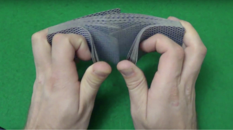 The photo shows a person's hand shuffling a deck of cards.