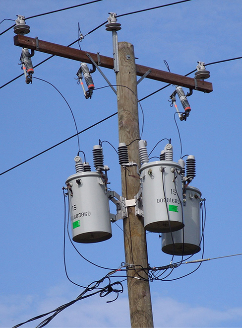 Photograph of transformers on an electric pole. There are three transformers, each encased in a cylindrical container.