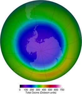 The map shows the variation in concentration of ozone over Antarctica. The scale for the total ozone level is depicted below the graph in Dobson units. The values are marked in colors of spectrum with the lowest value is marked in violet and the maximum value in red. The Antarctica region is marked in violet showing lesser ozone concentration and more ultraviolet rays. The region around Antarctica is in green, showing slightly higher concentration of ozone.