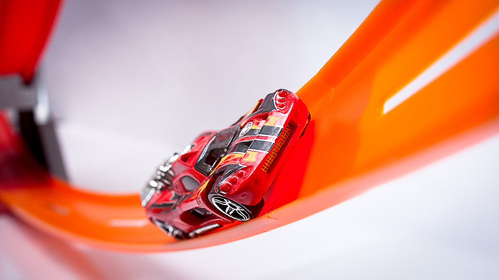A toy car is moving up a curved track.