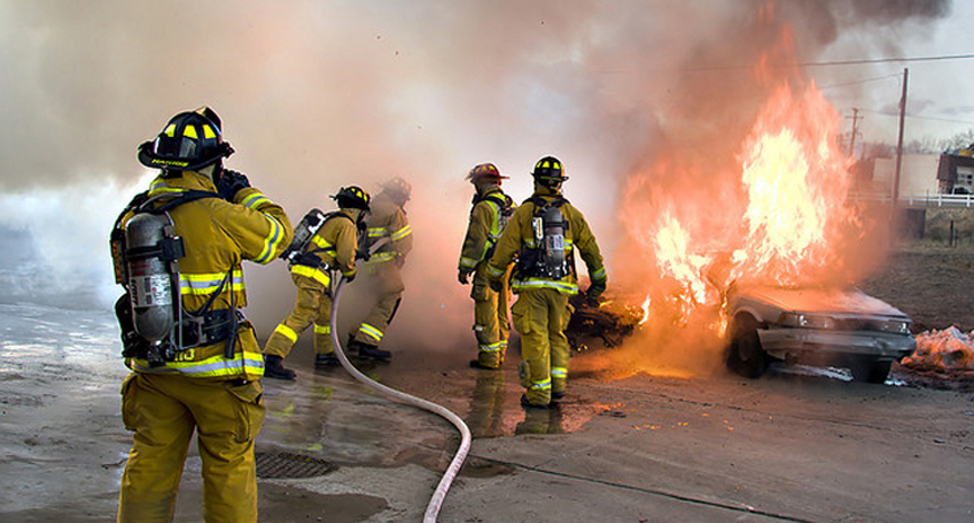 Photograph shows a group of firefighters in uniform using a hose to put out a fire that is consuming two cars.