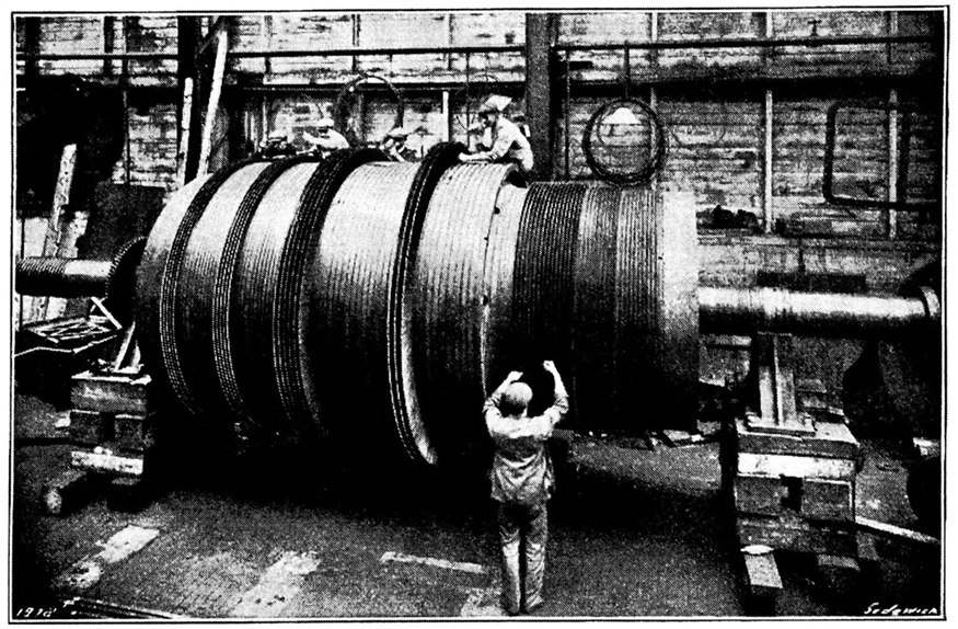 An old photo of a steam turbine at a turbine production plant. People are shown working on the turbine.