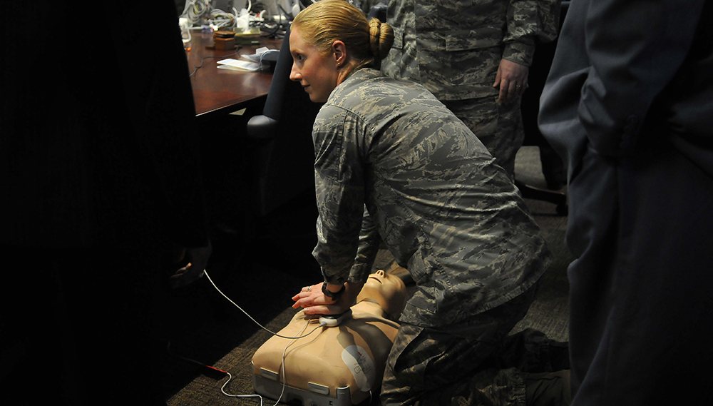 Air Force officials practice using an automated external defibrillator (AED). Electric potential energy is stored in the defibrillator unit and sent to resuscitate the patient.