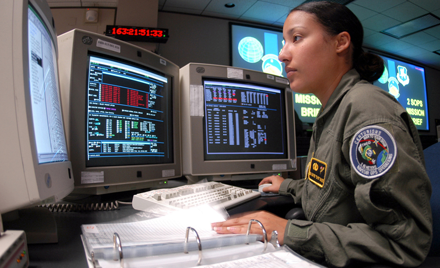 Photograph of a space systems operator using several computer monitors showing various data.