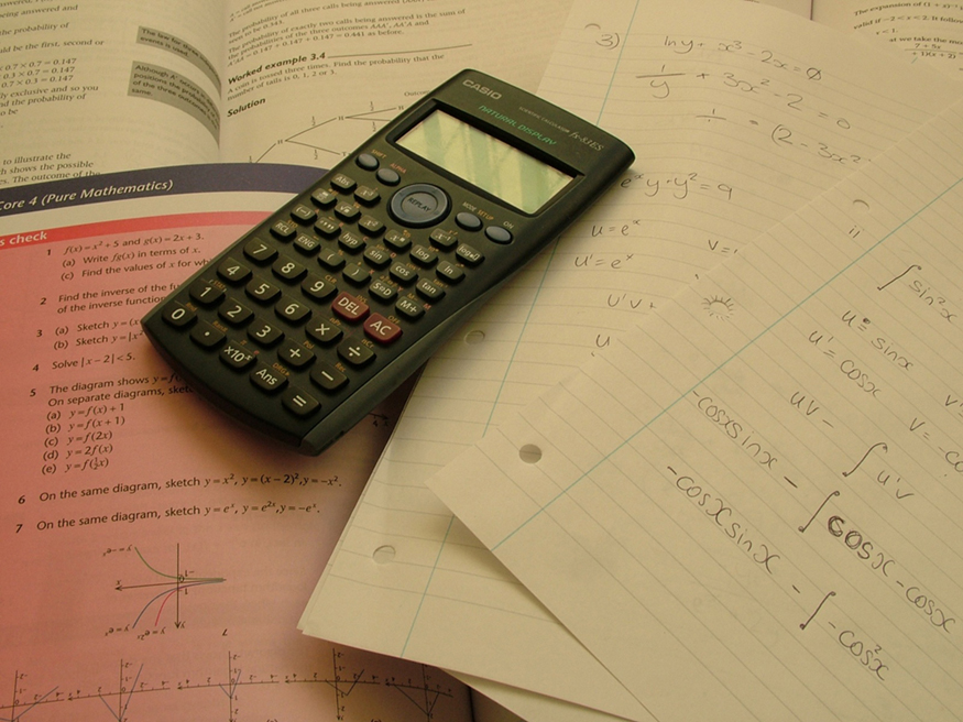 A calculator is placed on open math books and few papers. Problems on trigonometry are solved on one of the papers.