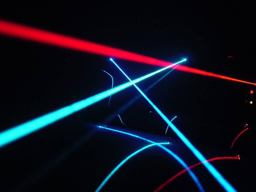The image shows several red and blue colored laser beams rays that look similar to searchlights.