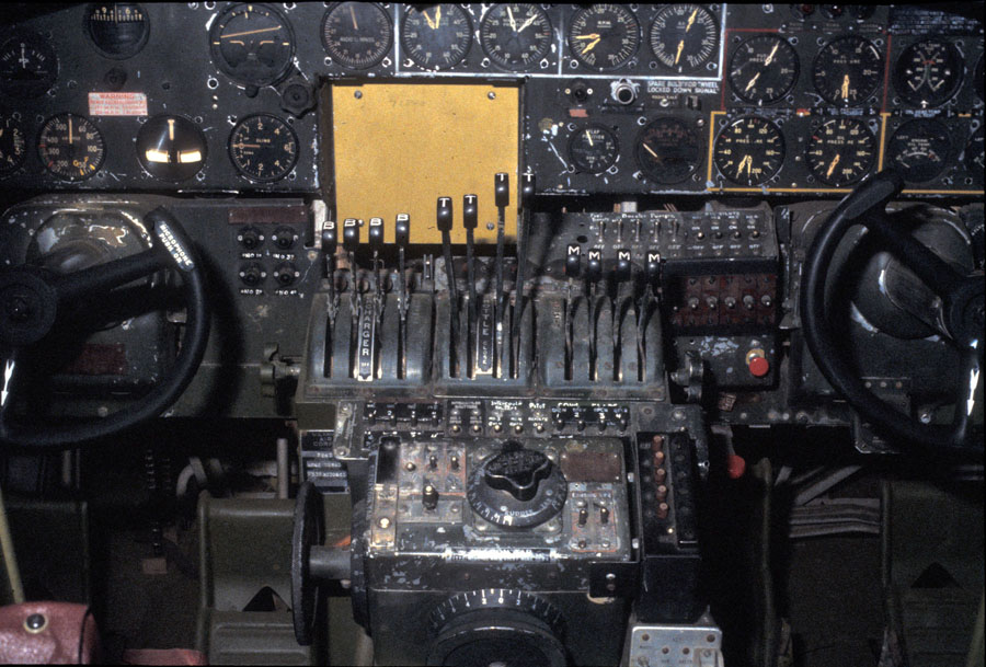 The image shows an aircraft panel with lots of dial indicators, some levers and two wheels.