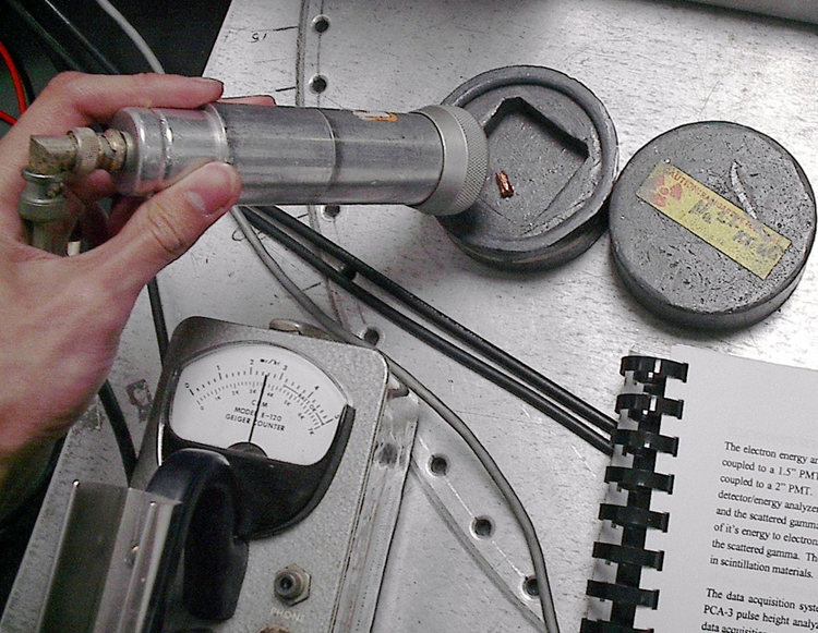 Image shows a person's hand holding a cylindrical object placed near a small piece of radioactive material. A dial indicator is connected to the cylindrical radiation detector.