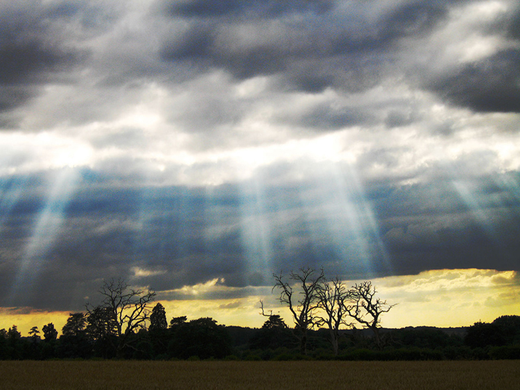 This figure shows Sun rays piercing clouds to illuminate a natural scene.
