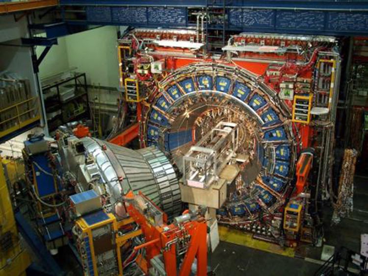 The image shows the picture of a huge cylindrical shaped proton decay detector with its main door open. It is as high as a double decker bus and as long as a small house. An untold number of cables, wires, and detector modules are arranged in a cylinder around a rectangular crate-like object containing another smaller cylindrical object.