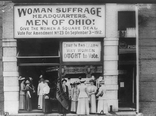 "This photo shows several women outside of the Woman Suffrage Headquarters. A large sign reads ""Woman Suffrage Headquarters. Men of Ohio! Give the Women a Square Deal. Vote for Amendment No. 23 on September 3, 1912."" A second sign reads, ""Come in and learn why women ought to vote."""