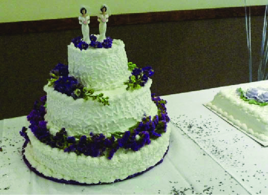 A photo of a cake with three tiers. Two human figurines appear on the top tier.