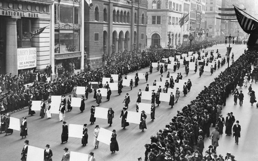 An image of a group of people marching down a street. Several pairs of people are carrying large signs between them. On both sides of the street is a crowd of observers.
