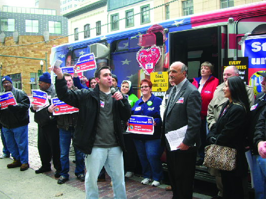 An image of a group of people standing in front of a bus. Some of the people hold signs.