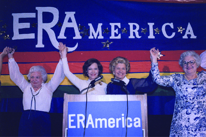 "A photo of Rosalynn Carter and Betty Ford speaking at a rally in favor of the Equal Rights Amendment. Signs on stage read ""ERAmerica."""