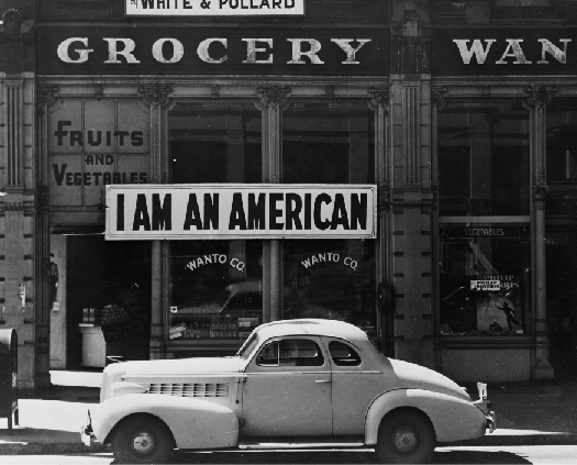 "A photo of sign in a store front that says ""I am an American."""