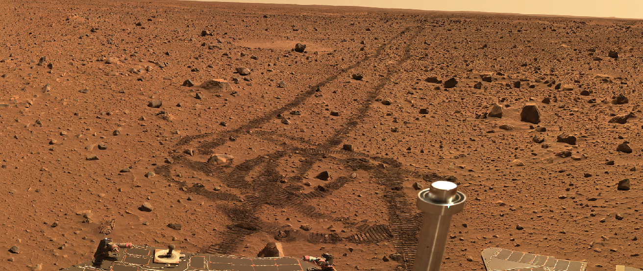 Spirit Rover on Mars. Beginning in the upper right of this photograph, the tracks left by the passage of the Spirit rover are visible on the flat, rock strewn martian terrain. At the bottom, the tracks form a loop where the rover changed direction, and portions of the rover's body are seen.