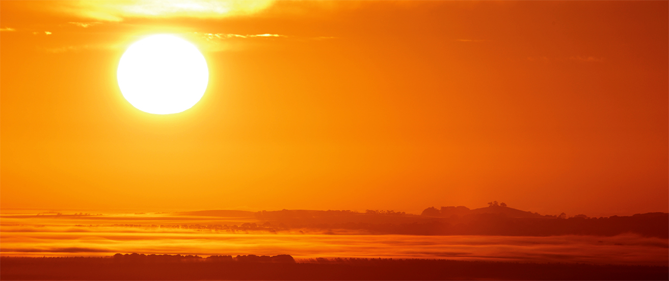 A photograph shows the sun low in the sky at sunset.