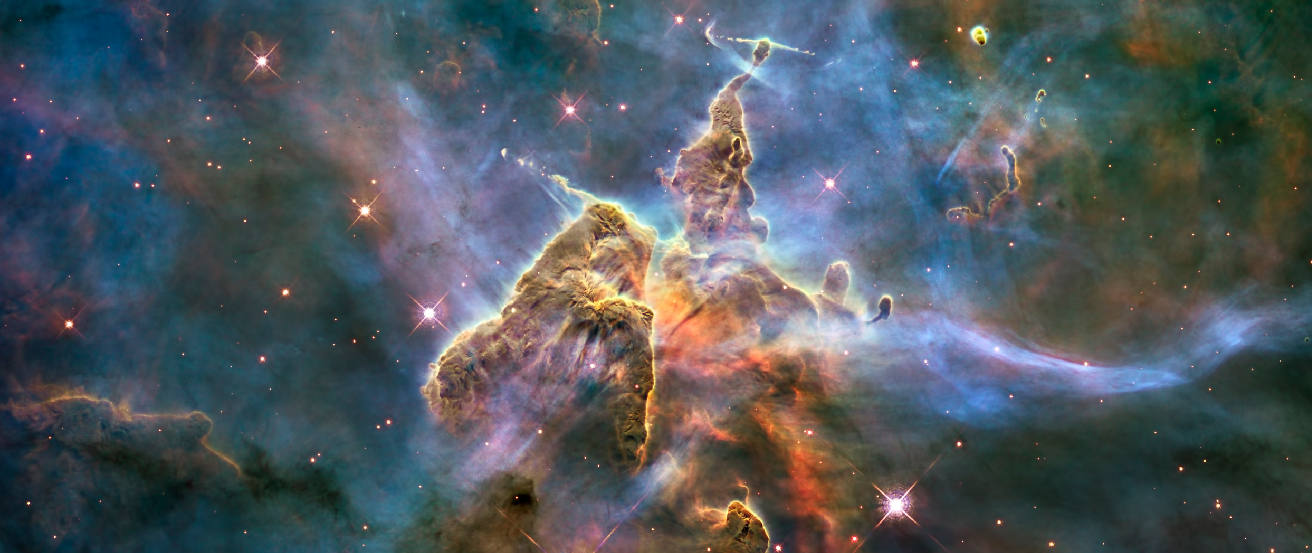 """The Carina Nebula. This image shows two cone-shaped nebulae within the larger Carina Nebula. At the very top, or apex, of each gaseous """"cone"""" are thin jets of material flowing into space at right angles from the cones."""