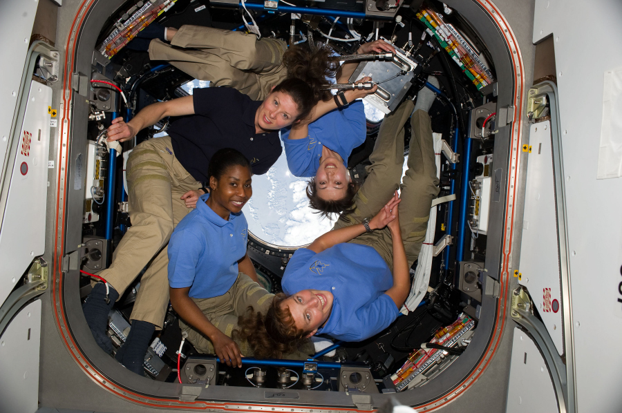 Photograph of four astronauts in free fall.