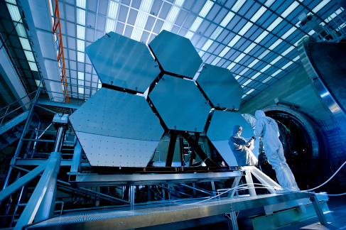 Photograph of the cryogenic mirror testing assembly and 6 of the hexagonal mirror segments of the James Webb Space Telescope. A technician is seen inspecting the right-most mirror segment.