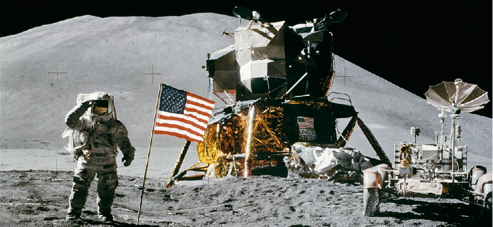 Photograph of Astronauts on the Moon. At center is the landing module, and to the right is the Lunar rover used by the Astronauts to travel large distances from the landing site. At left an Astronaut salutes the American flag placed near the lander. Scattered throughout the foreground are footprints in the Lunar soil.
