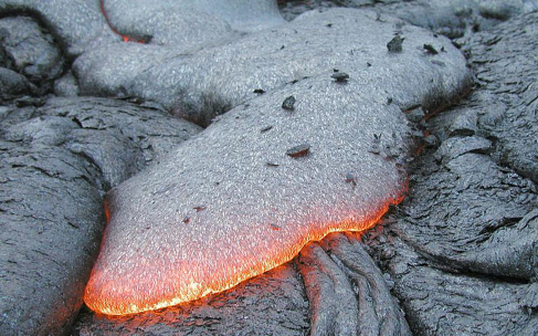 Image of a Lava Flow from a Basaltic Eruption. The leading edge of the flow is red-hot, while the surface behind has cooled to almost black