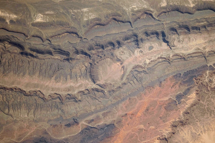 Photograph of an Impact Crater from Space. The large, circular Ouarkziz crater clearly stands out in the center of this image amidst the parallel lines of the mountains and ridges where it lies.