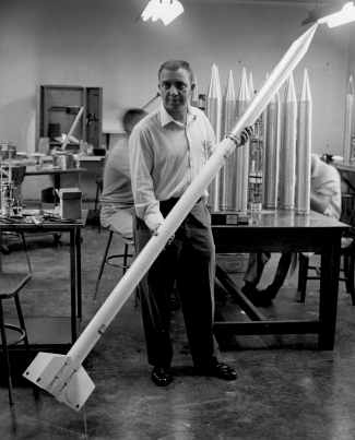"Photograph of James Van Allen holding a small rocket, which was part of a ""rockoon""."