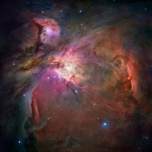 Photograph of the Orion Nebula. This image is dominated by large areas and bright swirls of glowing gas clouds, criss-crossed by dark bands of dust.