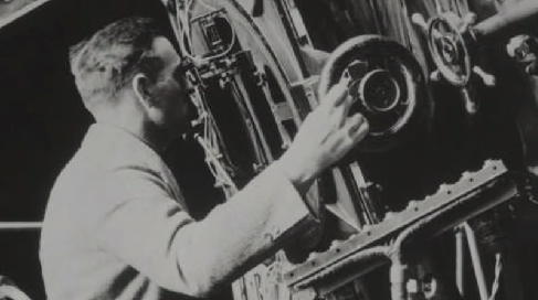 Photograph of Edwin Hubble, adjusting instrument settings as he peers through a finder-scope on the 100-inch telescope on Mt. Wilson.