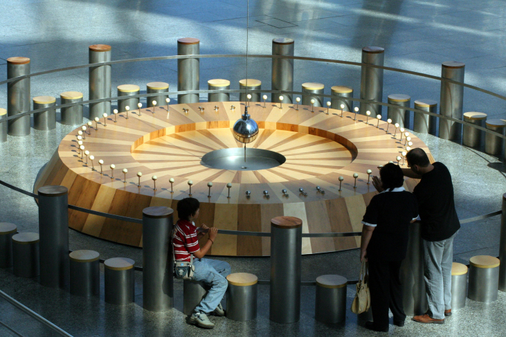 Photograph of Foucault's Pendulum. Several viewers watch the pendulum bob (silver sphere at center) as it swings over the circular wooden platform containing the targets it will knock over in the course of a day.