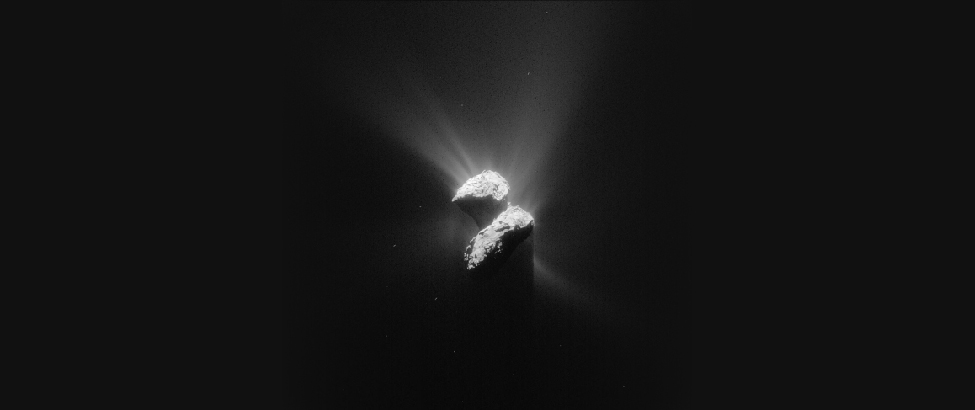 Image of Comet Churyumov-Gerasimenko (67P). Two lobes of this irregularly shaped object are illuminated by sunlight coming from the upper left. Bright streaks of material are seen radiating away from the sunlit surfaces of the comet. These streaks are not seen coming from the shaded portions.