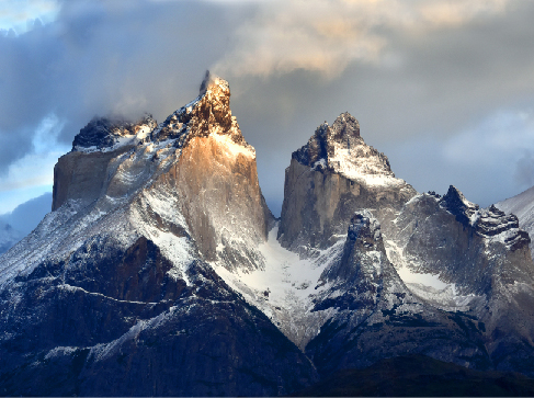 Image of the Torres del Paine mountains in Patagonia. The peaks of the mountains are sharp and jagged.