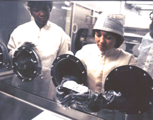 "Photograph of Technicians Examining a Lunar Sample. Two scientists look at a Moon rock through the glass of a scientific ""glove box""."