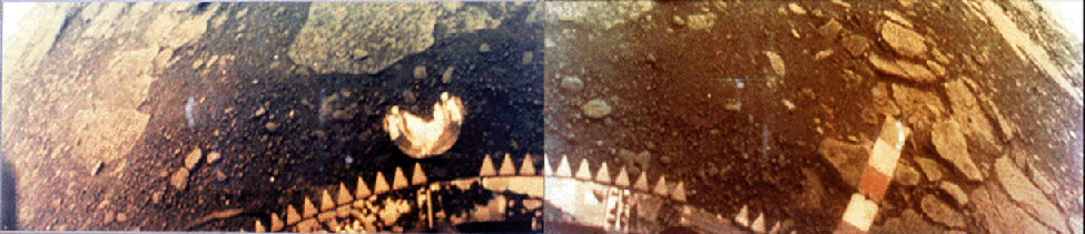 Fisheye view of the surface of Venus. The base of the Venera probe is visible at the bottom center of this photograph while flat rocks and dark soil stretch to the horizon at the upper left and upper right.