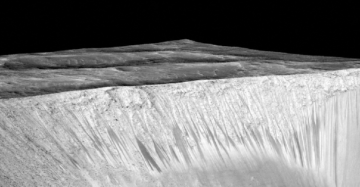 The wall of Garni crater. The wall of the crater comprises the lower half of this image. The dark streaks that run nearly vertically on the lower half of the crater wall are clearly visible.