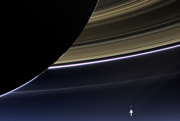 Image of the Earth from Saturn. The Earth appears in the distance as a pale blue dot (arrowed at lower right) below Saturn's rings in this dramatic image from the Cassini orbiter. The night side of Saturn is seen at upper left, with the backlit rings covering the remaining top half of the image.