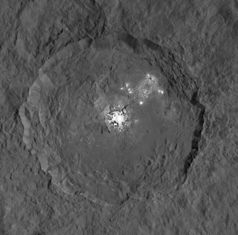 Occator Crater. In this view, looking directly down on Occator, bright features are seen on the floor of the crater at center and in the upper right.