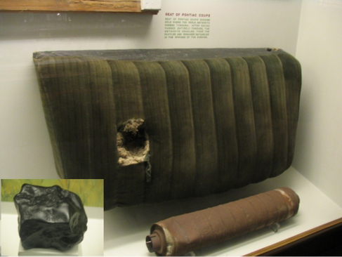 A photo of a car seat preserved in a museum, with a hole in it left by a meteorite. In the corner is a smaller photo of the Benld meteorite.