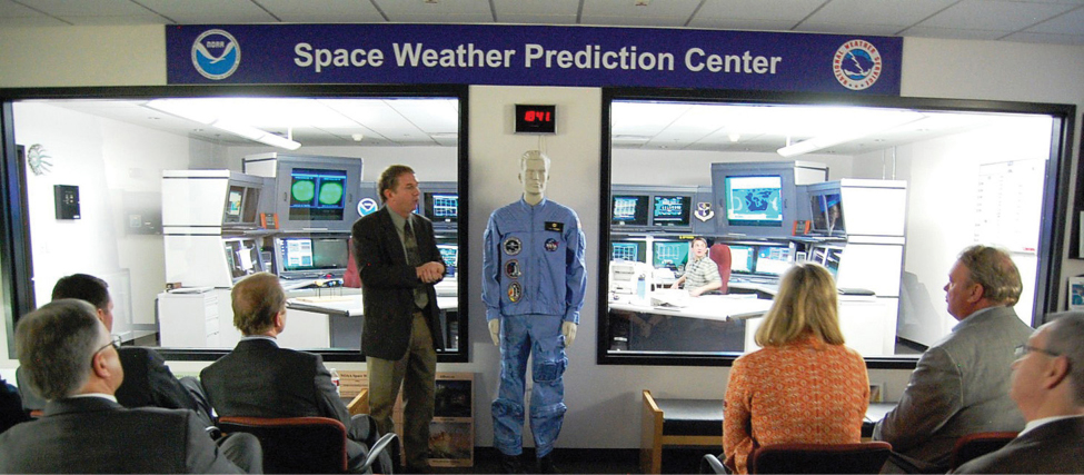 "An image of several seated people in a room with a banner reading ""Space weather prediction Center."" At the front of the room a person stands and addresses the seated people."