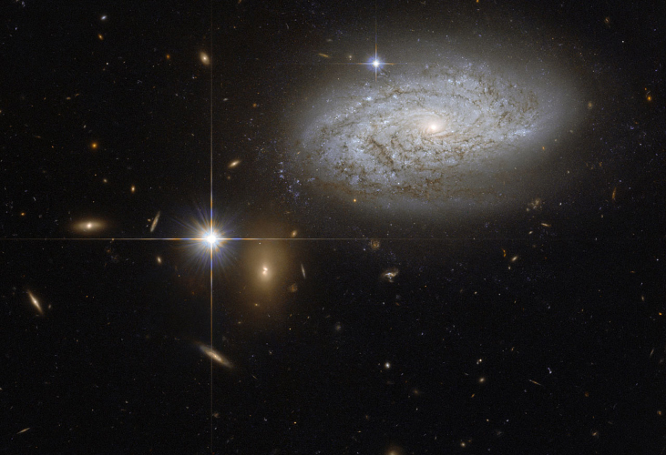 Type Ia Supernova. The very bright star to the left of center is a type Ia supernova at the outskirts of the spiral galaxy seen at upper right.