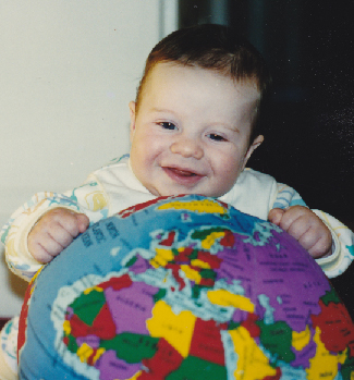 Photograph of an infant human, playing with a toy globe of the Earth.